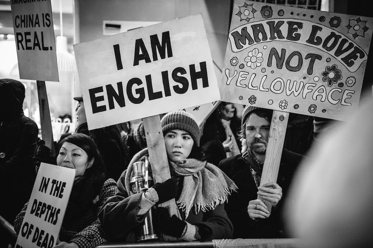People at an anti-racism protest holding placards