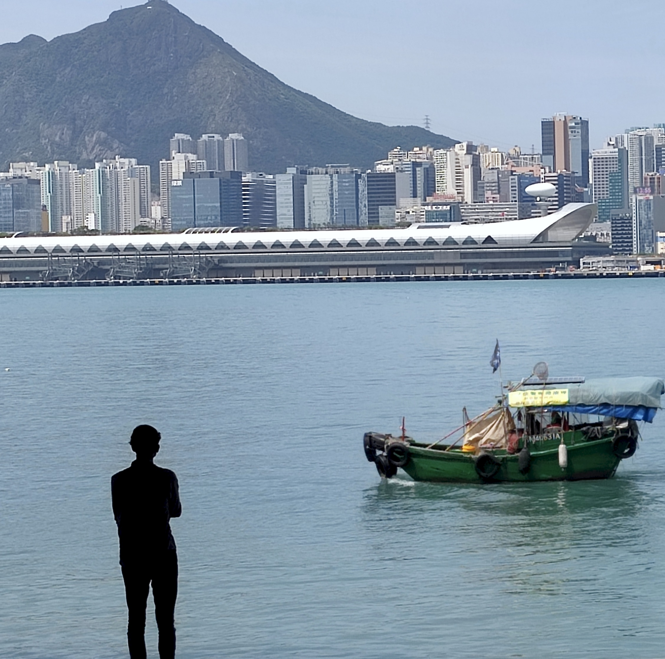 Kai Tak Cruise Terminal with fishing boat and figure in foreground
