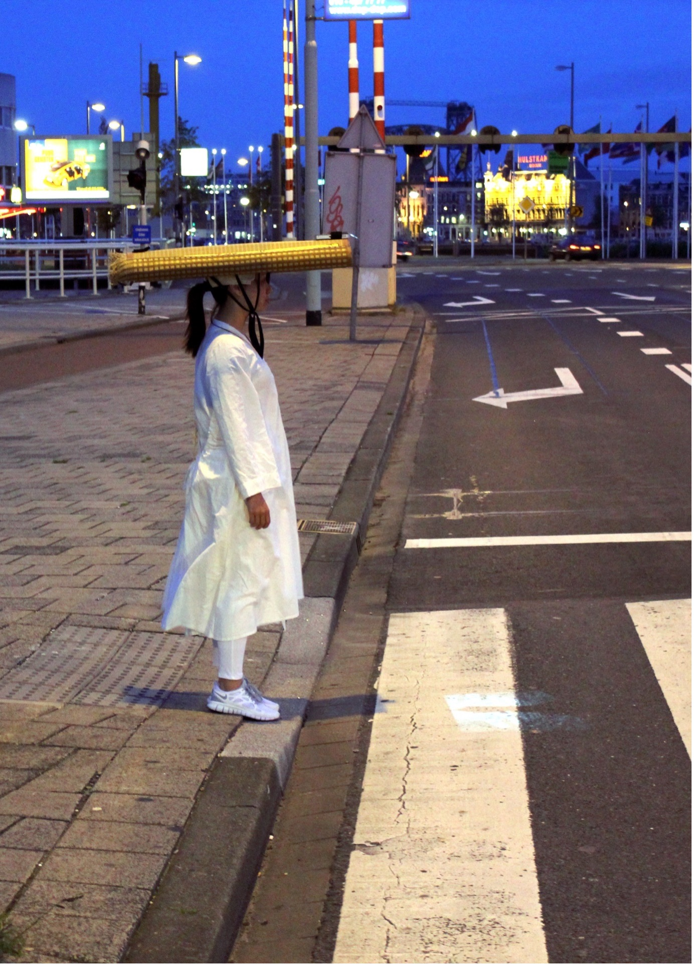 Woman in white with yellow headgear crossing the road